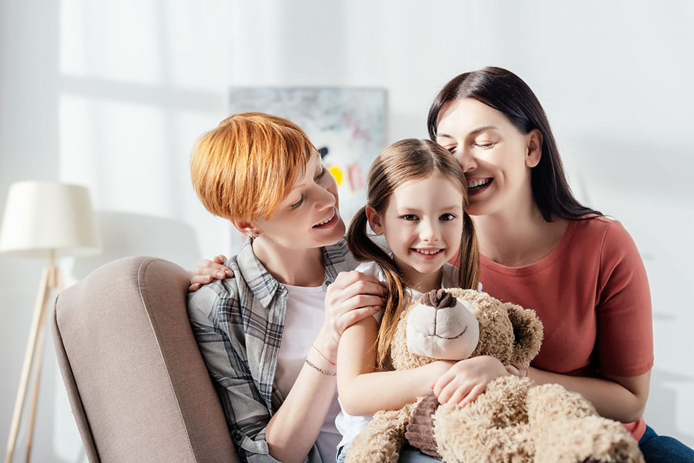 Smiling kid with teddy bear looking at camera near happy same sex parents on sofa at home