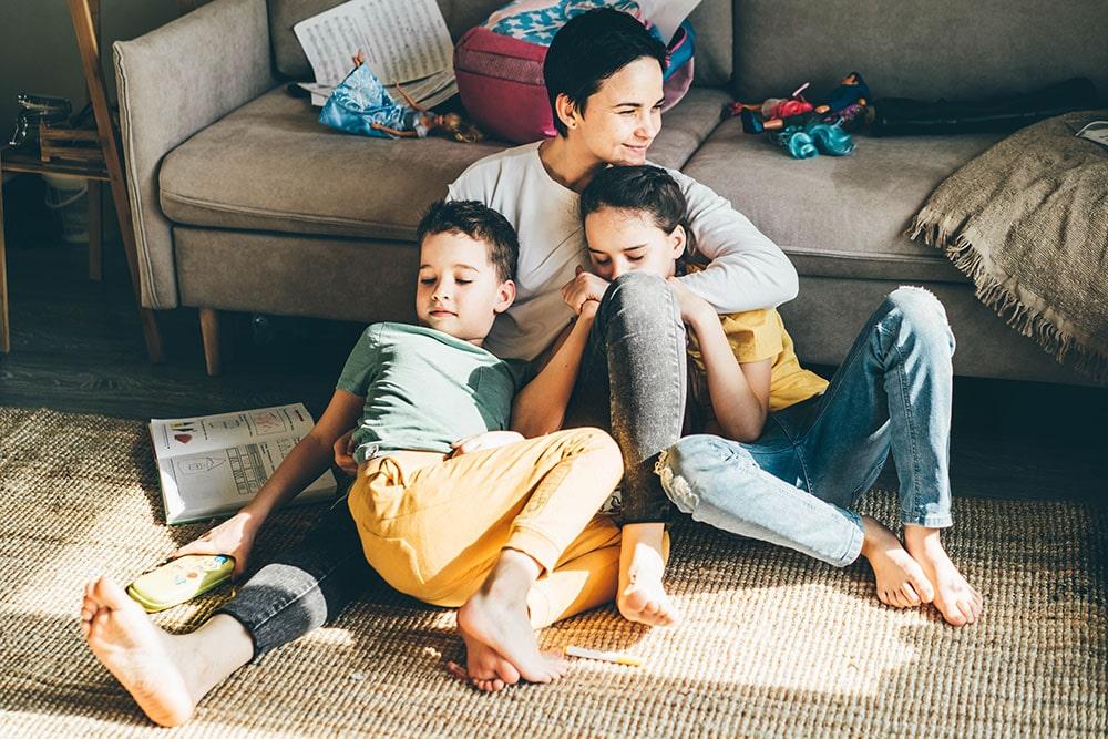 Happy mother hugs her children siblings on floor.