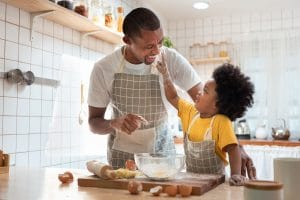 African Father and son baking cookies at home together.