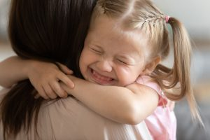 Funny little child girl smiling embrace foster care parent mum, adorable sweet small kid adopted daughter cute face hug mother caretaker holding tight feel happy express love get new family concept