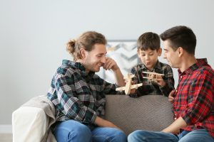 Happy gay couple playing with adopted child at home