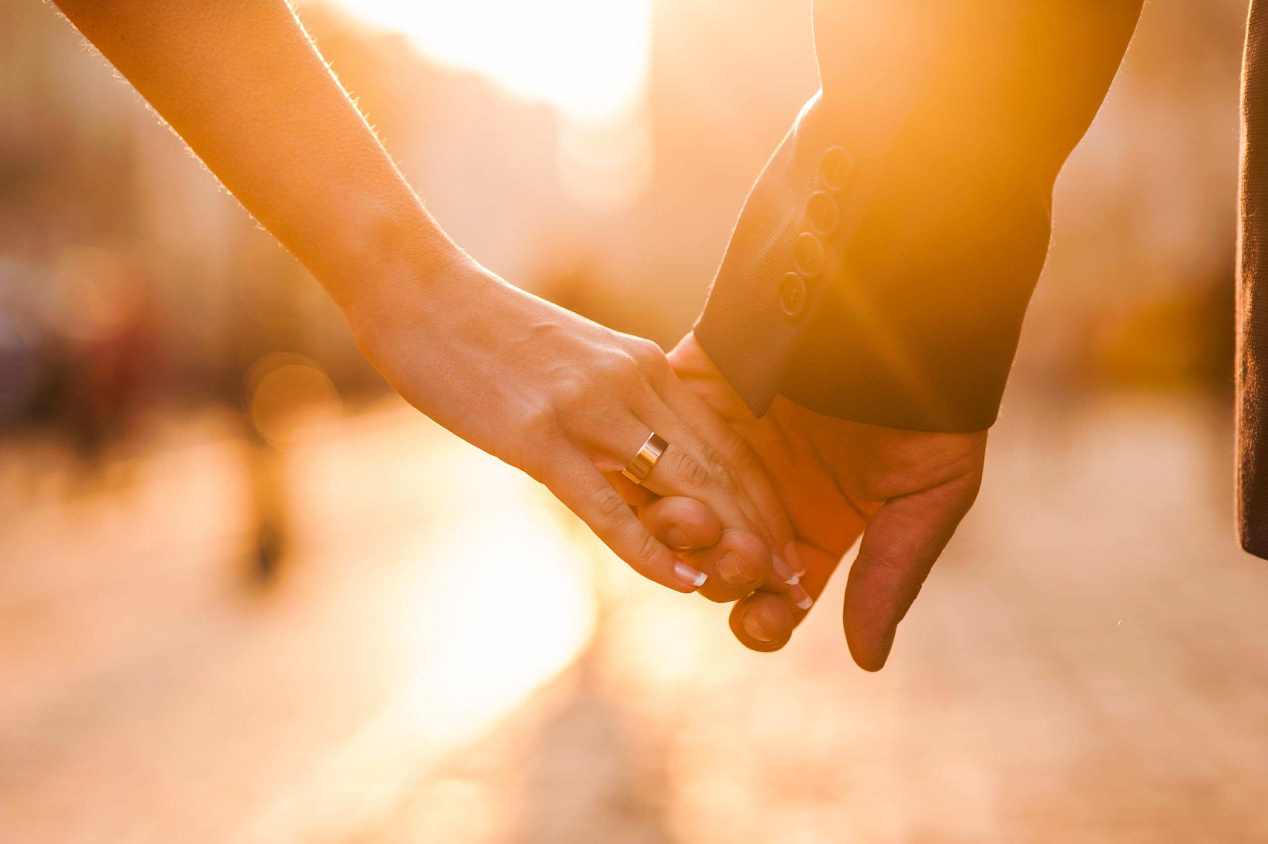 Beautiful couple holding hands at sunset