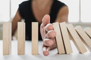 Business mediator stopping falling wooden dominos with hand dispute settlement mediation consultant advisor solving conflicts problems